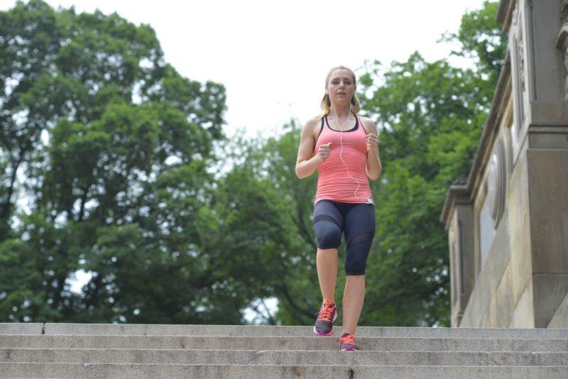 木々をバックに階段を駆け下りている女性