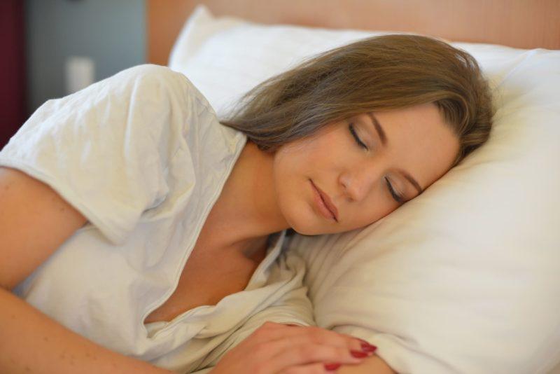 ホテルでヨレヨレのTシャツで寝ている外国人女性