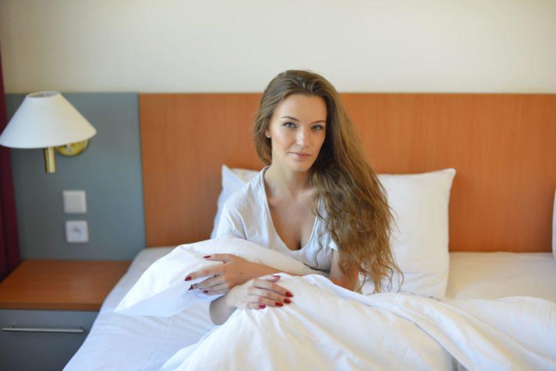 朝、ホテルでベッドから起き上がったばかりの女性