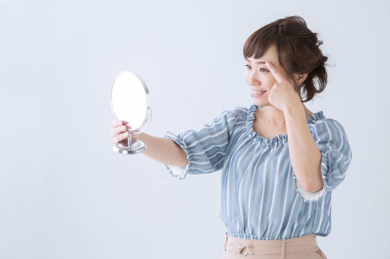 眉毛の状態を鏡でチェックしているブラウスの女性
