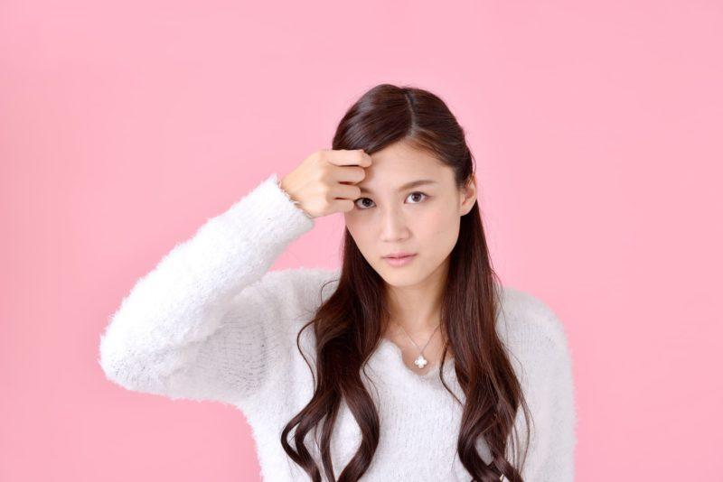 前髪を触っている白いニットを着た女性