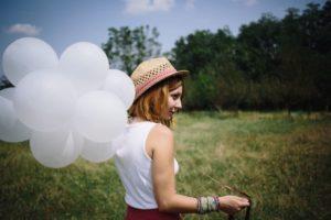 晴れた草むらの中で麦わら帽子の女の子が白い風船を持っている