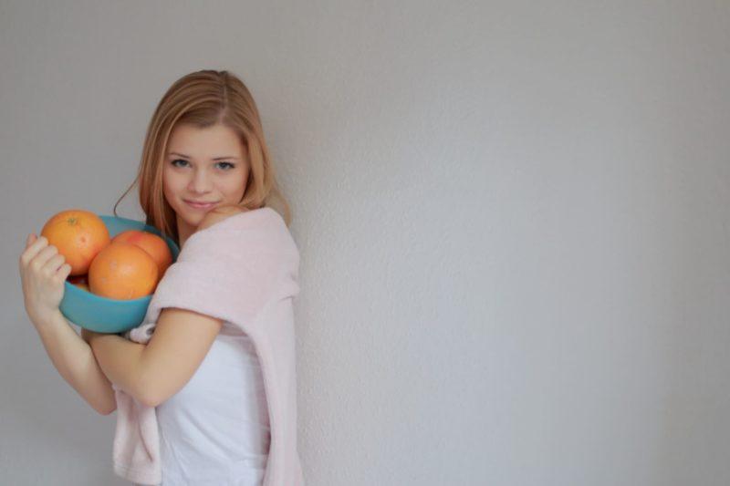 大きなオレンジを持って部屋に行こうとしている女性