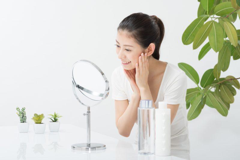 鏡を見てスキンケアをする女性