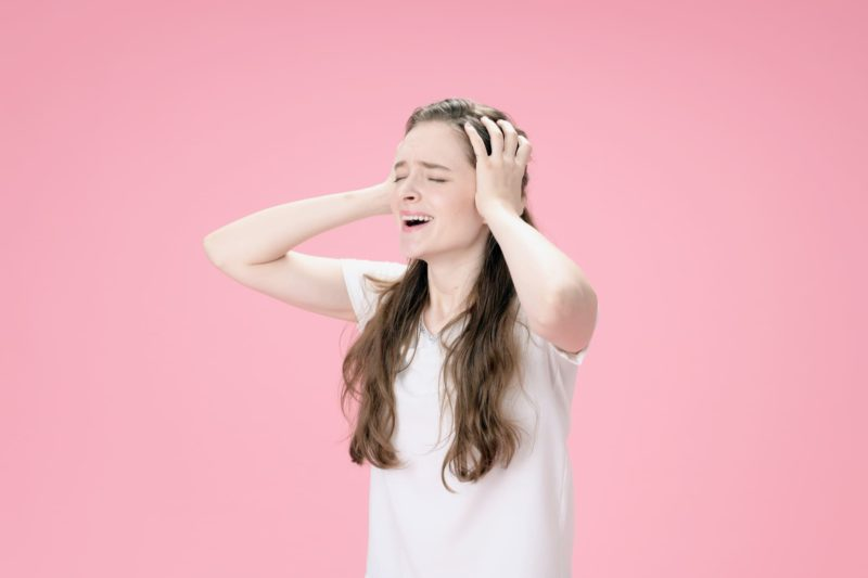 頭を抱える髪の長い外国人女性背景ピンク