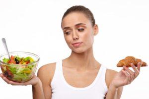 右手にサラダ左手にパンを持つ外国人女性