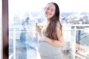 日の当たるベランダで水を持って微笑んでいる妊婦