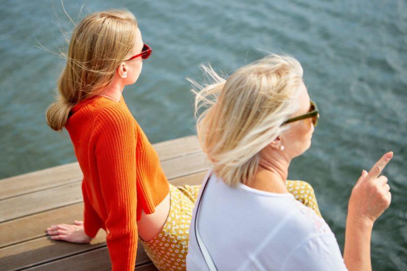 海沿いに座り景色を眺めている女性二人の後頭部