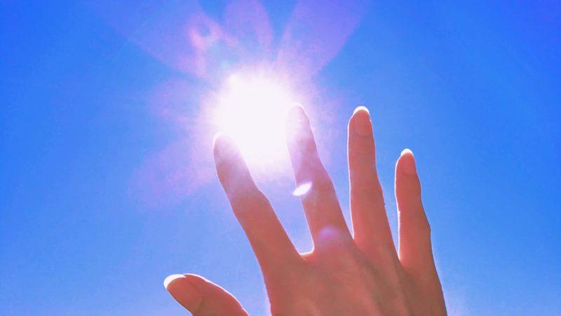 サンサンと光と紫外線が降り注いでいる太陽に手をかざす