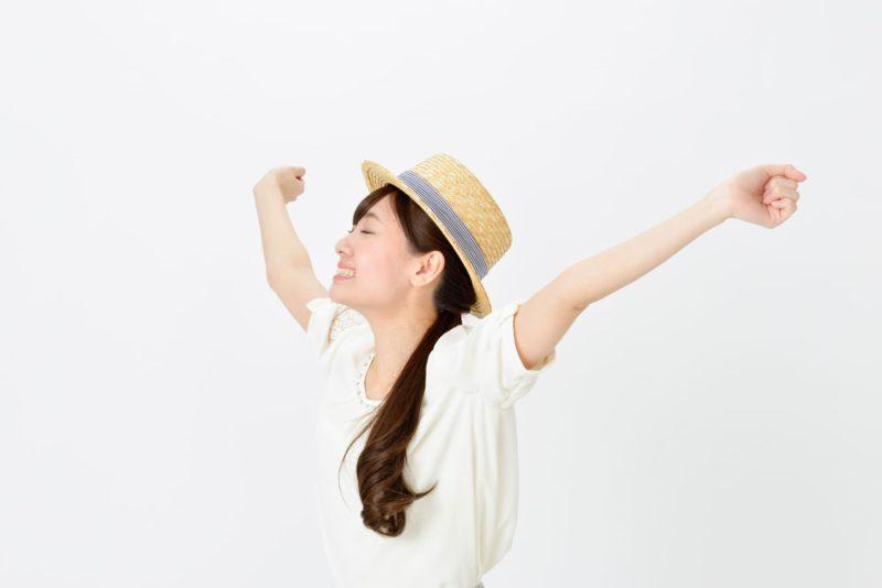 カンカン帽をかぶって両手を気持ち良さそうに挙げている女性