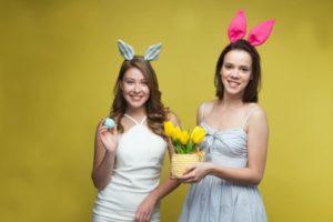 黄色い背景で卵と黄色いチューリップを持っている女性