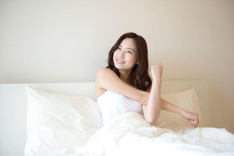 すがすがしく起きて朝日を浴びている寝床の女性