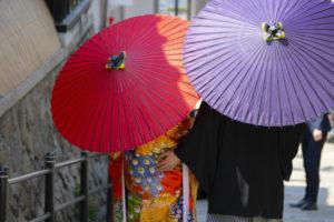 和装をしてピンクと紫の番傘を差したカップルの後ろ