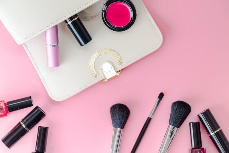 ピンクの床に撒かれたバッグから出た化粧品達