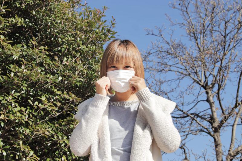 青い冬空の中、マスクで顔を隠している女性
