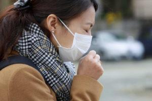 寒い外気の街中でマスクをして咳をしているご婦人