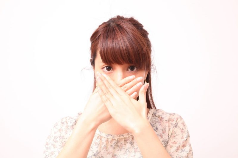 口の中が臭いと手で口を塞いでいる女性