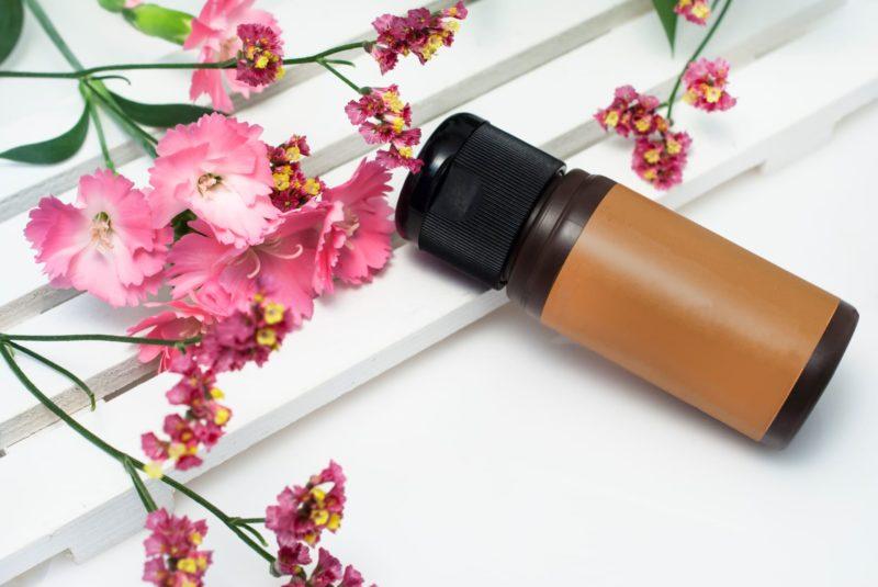 ピンクの花が添えられている茶色い瓶の美容液