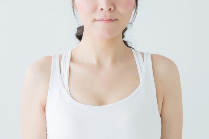 Uネックの白いタンクトップを2枚重ねて着ている女性