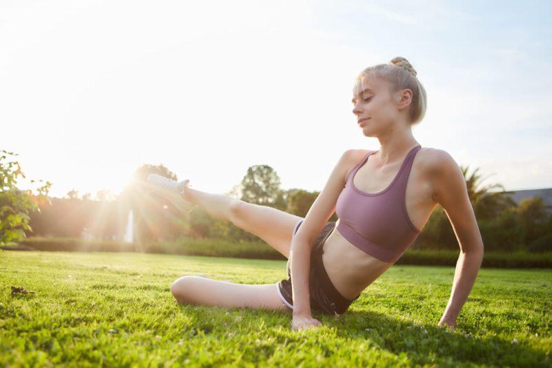 太陽に向かって足を上げてストレッチをしている女性
