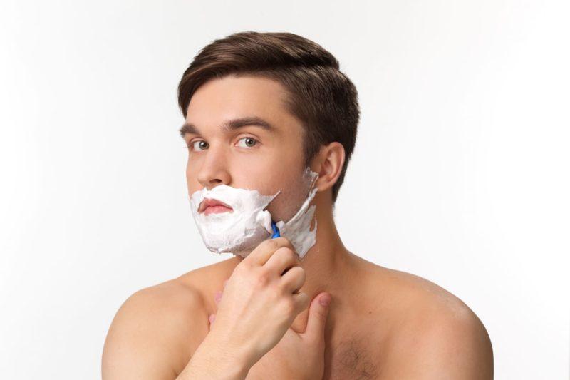 シェービングクリームを付けて髭を剃る外国人男性