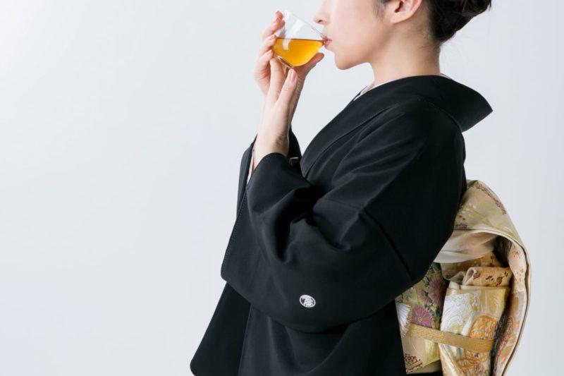 漢方か何かの飲み物を飲んでいる黒い着物の女性