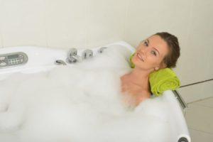 緑のタオルを敷いて泡風呂の中でこちらを見ている女性