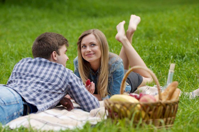 芝生でうつぶせになってピクニックをしているカップル