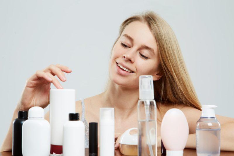 何本も並ぶ化粧品を選ぶブロンド長髪の白人女性