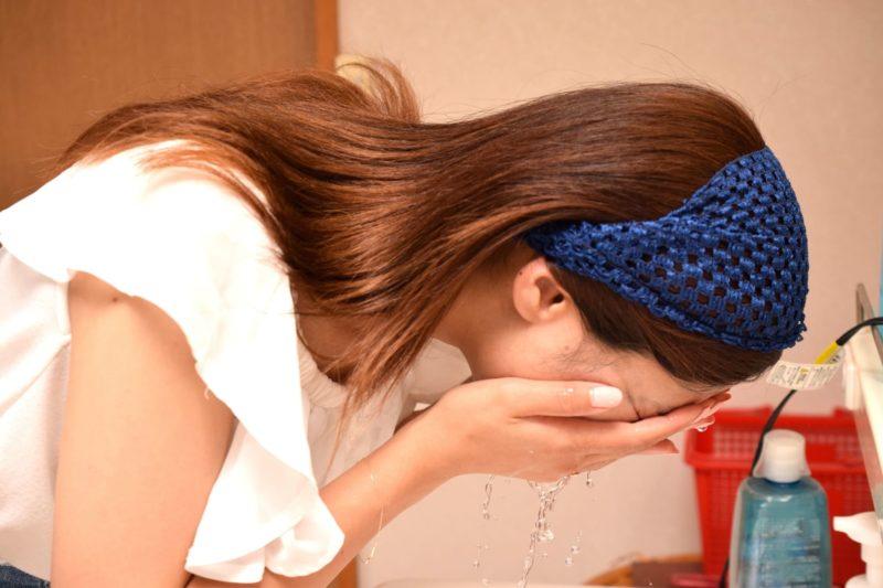 洗顔をする青いヘアバンドをしたロングヘアーの女性の横顔