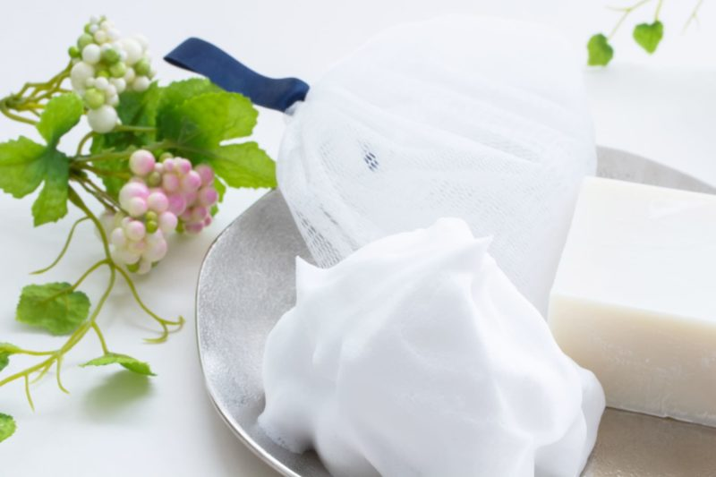 皿の上に洗顔ネットと泡と白い石鹸
