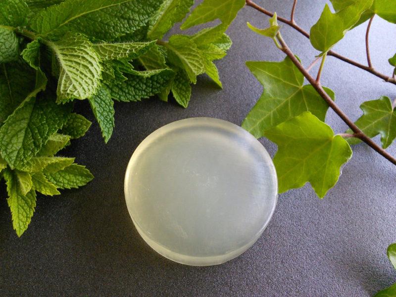 黒いテーブルの上の乳白色で半透明な石鹸と葉っぱ