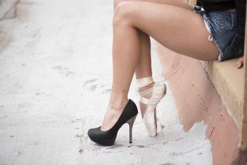 左右で違う靴を履いて腰掛けているショーパンの女性の足
