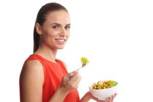 サラダを食べているオレンジのノースリニットを着ている女性