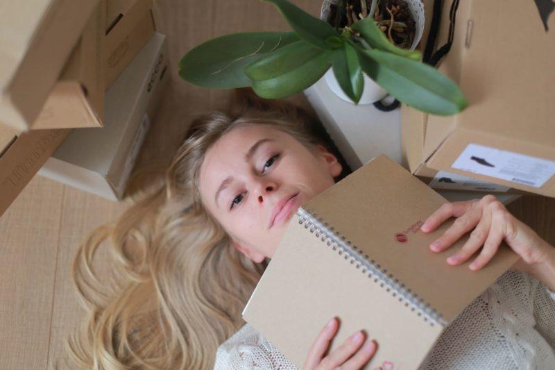 床に物がいっぱい置かれている中にノートを広げながら床に寝転ぶ女の子