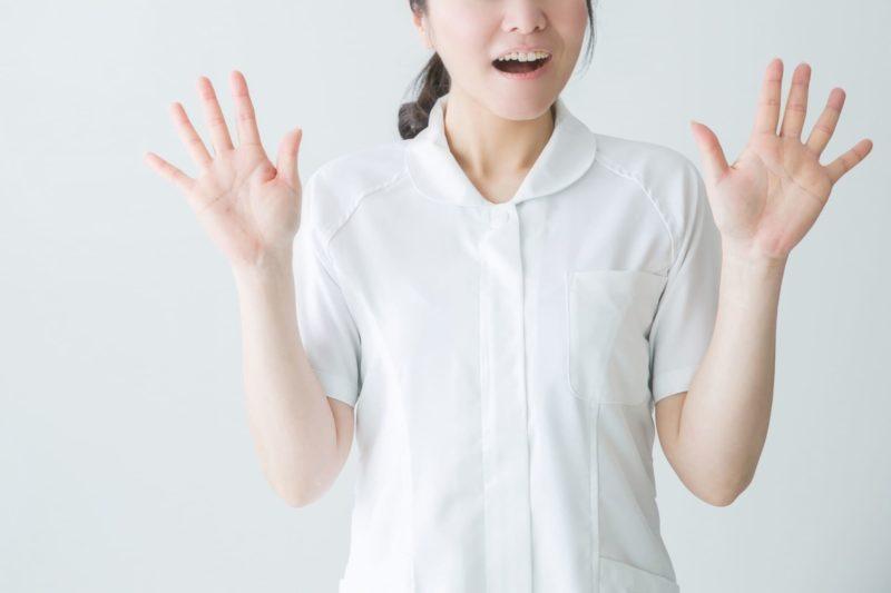 両手を出して驚いている白い服の女の人