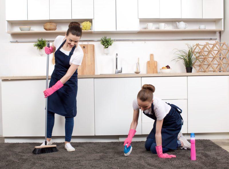 紺のエプロンをして台所を掃除している女性二人