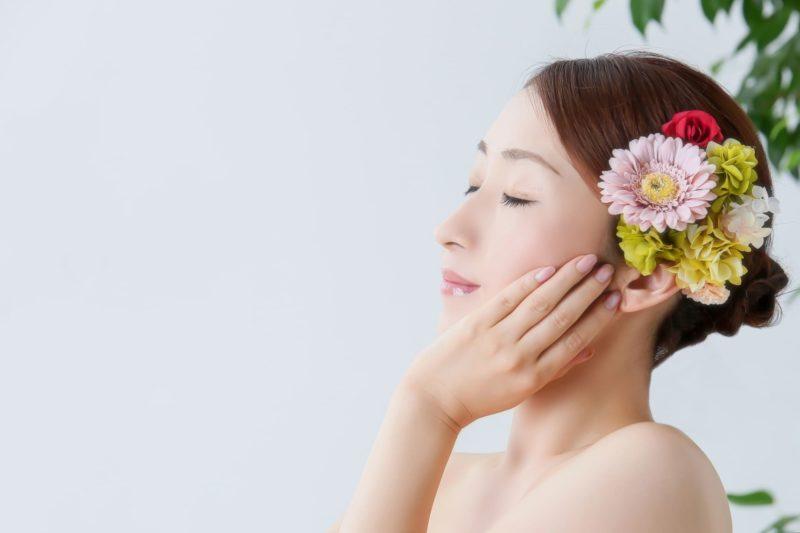 頬に手を当てて目をつぶる花飾りを付けた女性