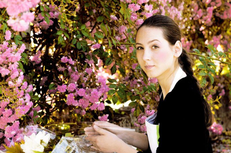 ピンクの花を手入れしている花屋の三つ編みした女性
