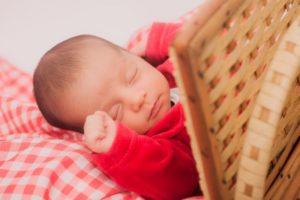 竹の衝立の側でお昼寝をしている赤いおべべの赤ちゃん