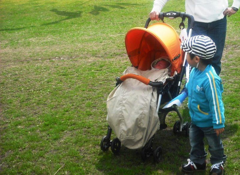 芝生の中お散歩に着ている新生児とそのお兄ちゃん