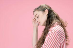 ピンクの背景で疲れていそうな眠そうな女性の横顔