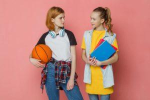 ピンクの背景で同級生と語らう10代の男女