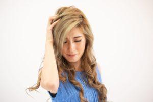 頭を抱えて悩んでいる青い服の金髪女性