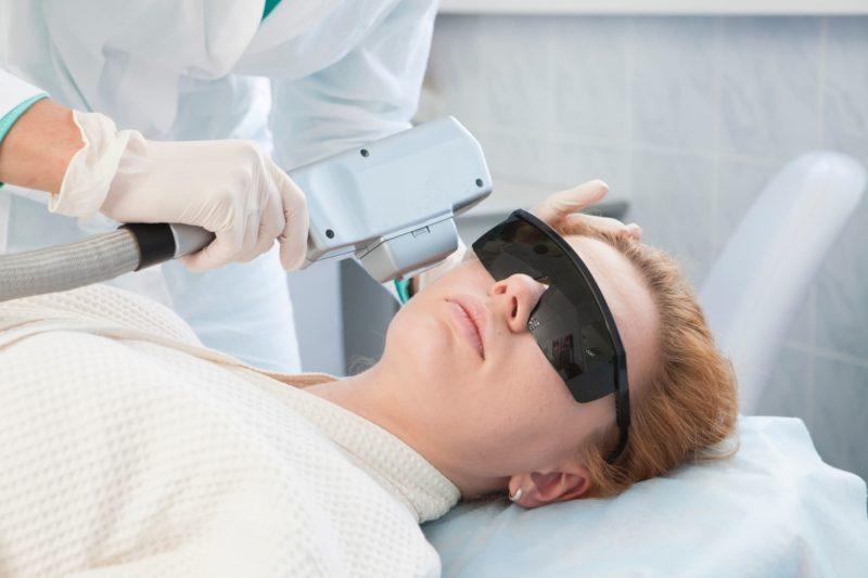 医療用レーザーを当てられている白人女性