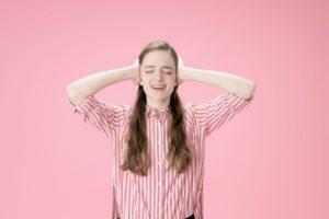 頭を抱えて声を上げるピンクストライプシャツの白人女性