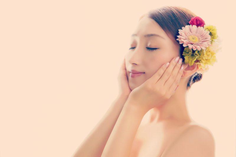 花の髪飾りをつけて頬に手を当てる女性