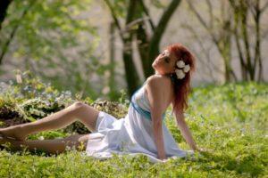 草原で座る赤毛の女性