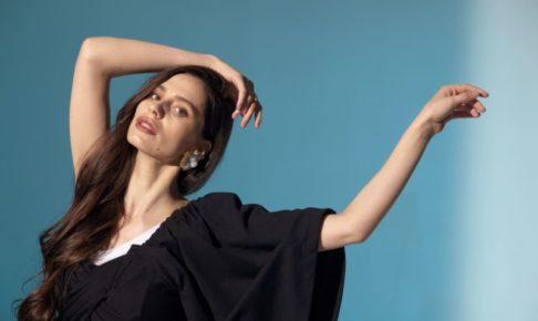 黒い服を着てモデルっぽいポーズをとる白人女性