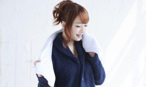 紺のパジャマを着て白いタオルを首にかけているお風呂上がりの女性